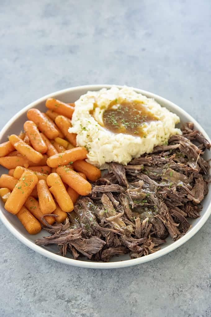 instant pot roast on plate with mashed potatoes and carrots