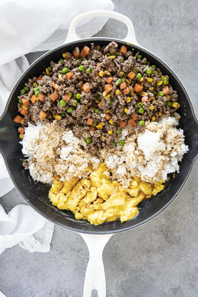 ground beef with vegetables rice eggs in skillet