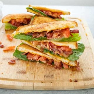 blt with cheesy garlic bread stacked on cutting board
