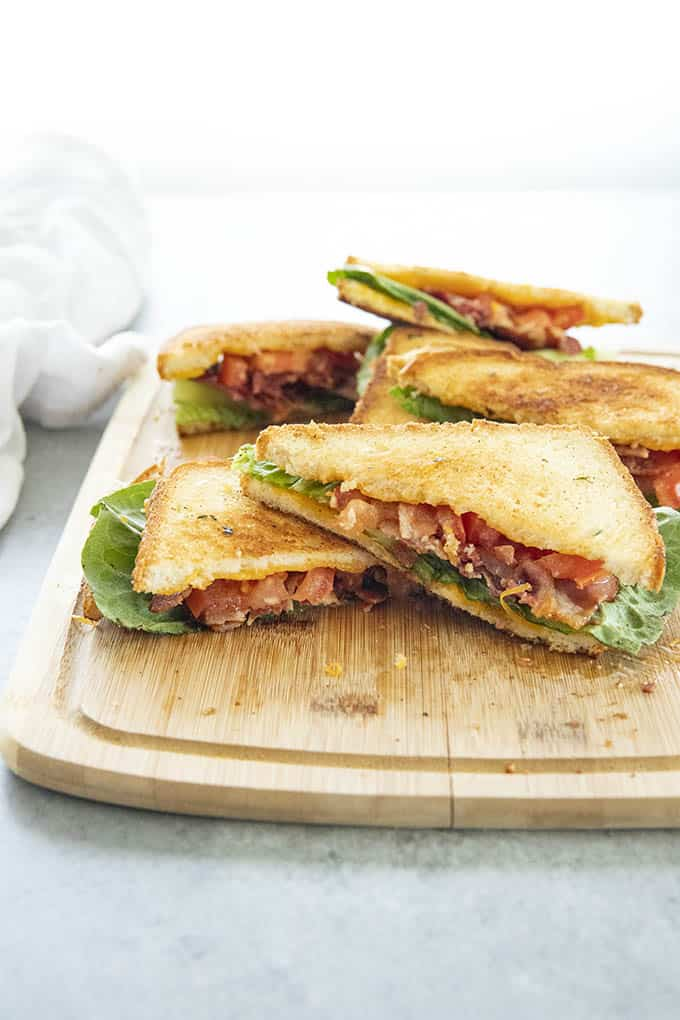 stacked cheesy blt on cutting board