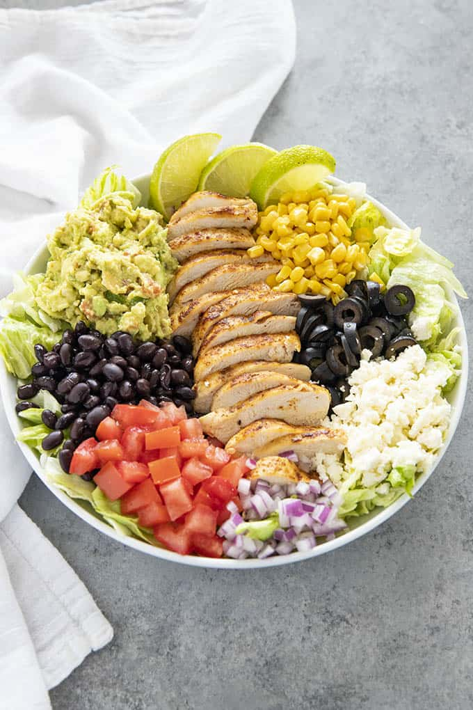 salad in a bowl with chicken and toppings