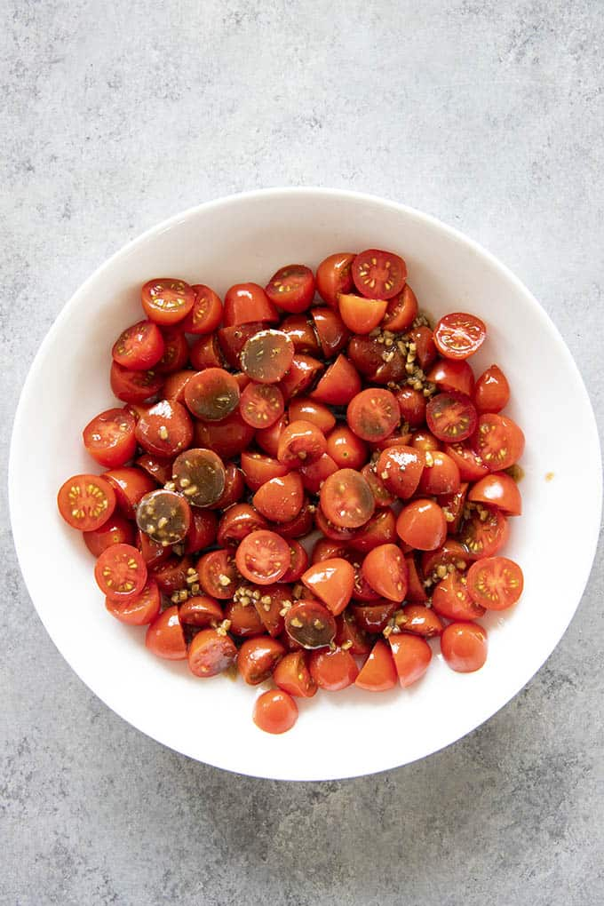 tomato salad with dressing in a white bowl