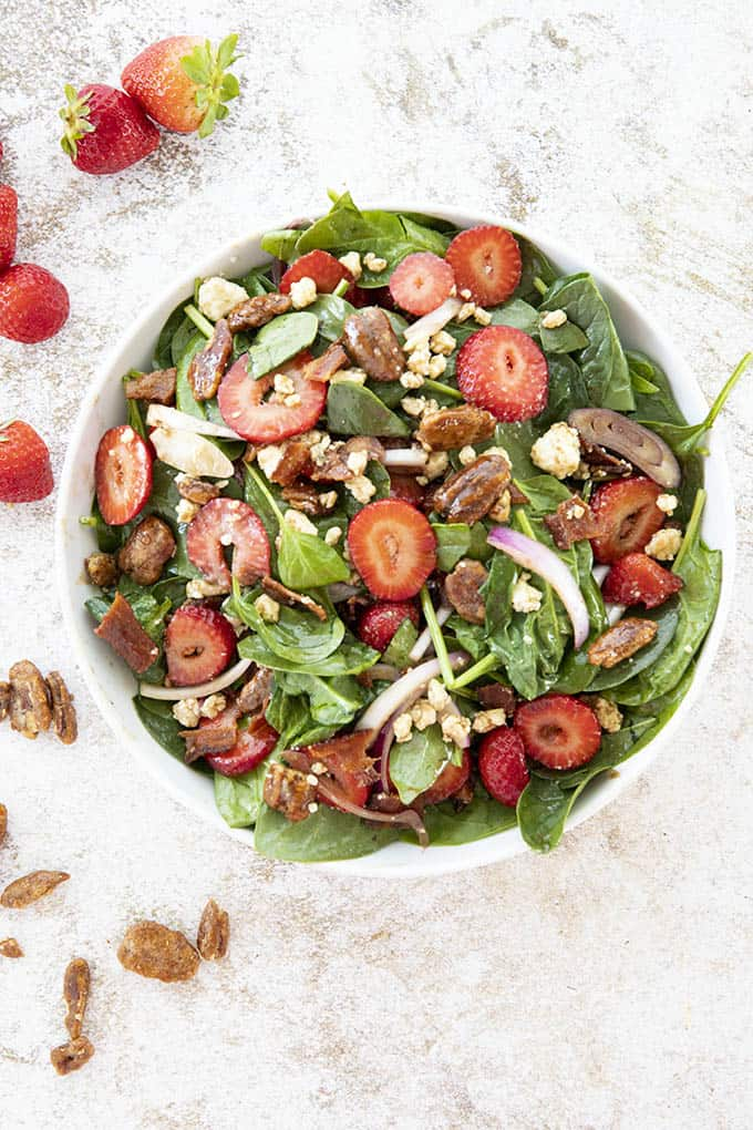 tossed spinach salad in a white bowl