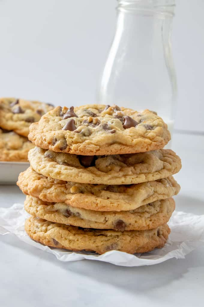 Chocolate chip cookies stacked on top of piece of parchment paper in front of glass of milk