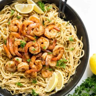 Cajun shrimp pasta in a pan with lemons and parsley
