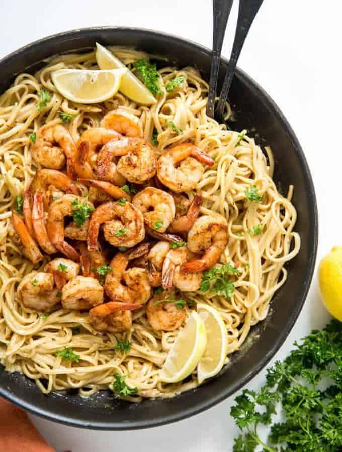 Cajun shrimp pasta in a pan with lemons and parsley