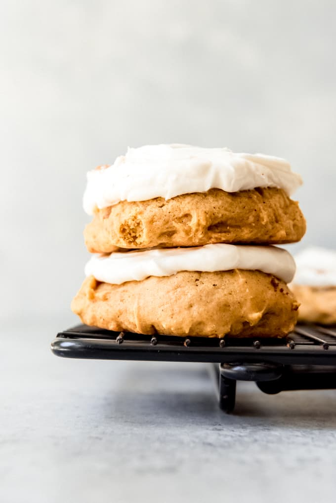 An image of two soft pumpkin cookies frosted with cream cheese frosting.