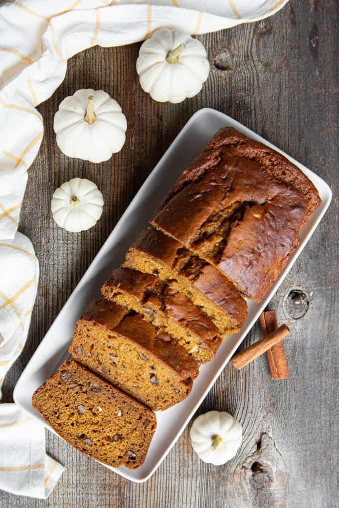 top view of sliced pumpkin bread loaf with white mini pumpkins