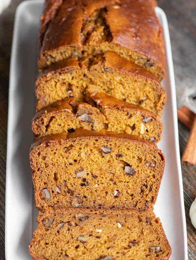 sliced loaf of pumpkin bread on white rectangle platter