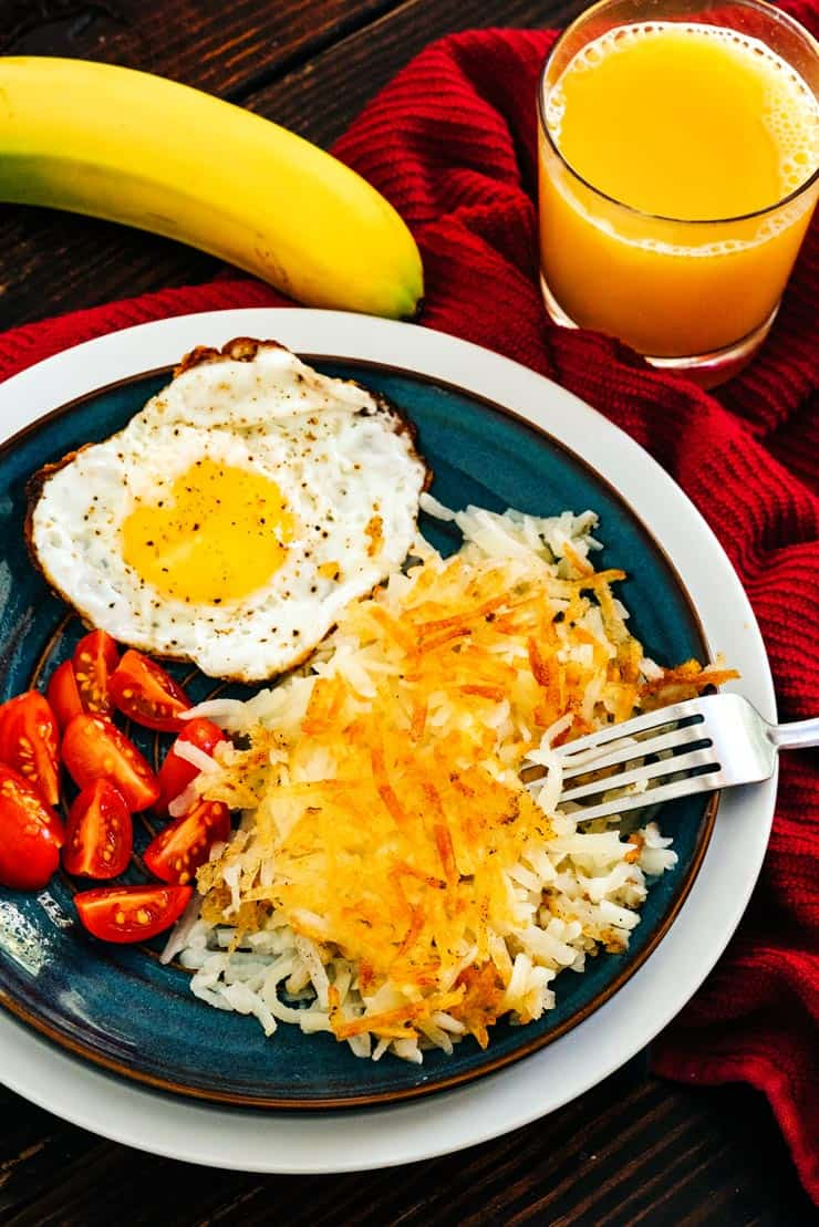 Homemade Hashbrowns on a plate with fried egg and tomatoes