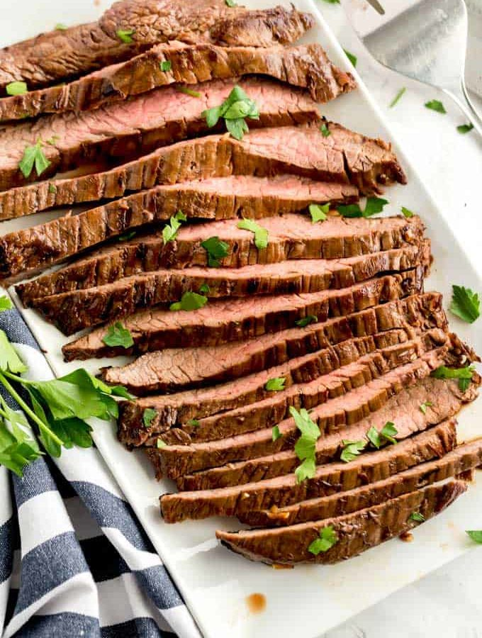Slices of pan seared London broil on a white platter.