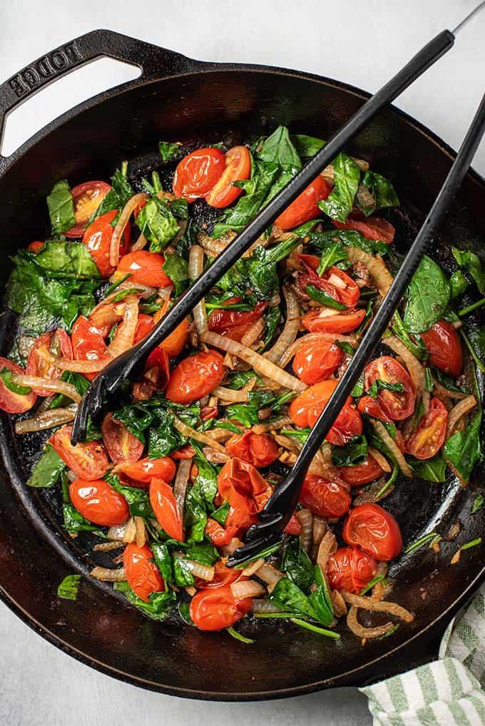 tomates cerises et épinards cuits dans une poêle